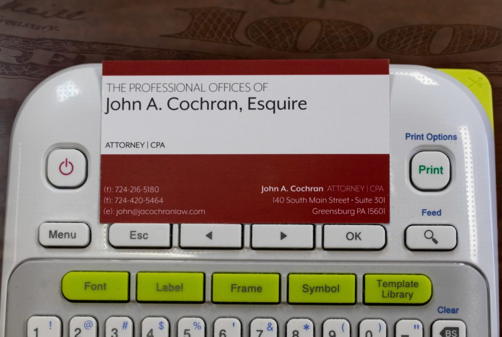 a photo of a business card holder for John Cochran. Decide whether you need a CPA or tax attorney for your needs.